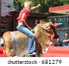 young female mechanical bull rider 3 - stock photo
