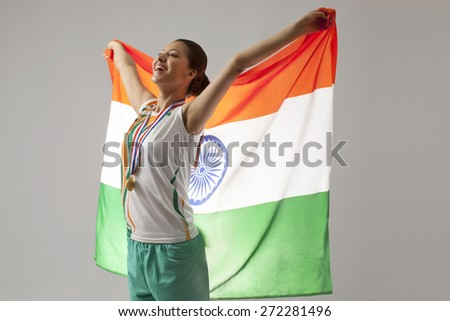 Young female medalist celebrating victory with Indian flag isolated over gray background - stock photo