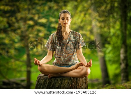 Young female meditate in park. - stock photo