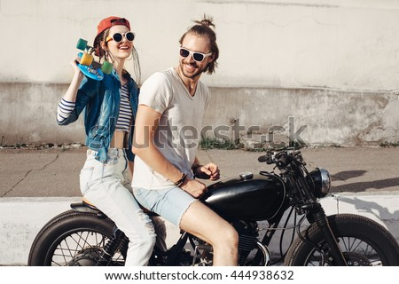 Young female model holding skateboard. Young man and woman sitting on vintage custom motorcycle on sunny day