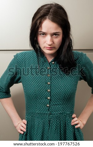 Young female model looking angry at the camera with a metal wall as a background - stock photo