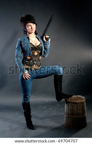 Young female model posing in studio with a toy shotgun, on black - stock photo