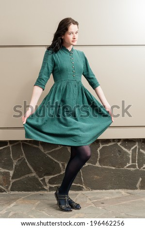 Young female model presenting her beautiful green dress with white dots in front of a stone and metal wall - stock photo