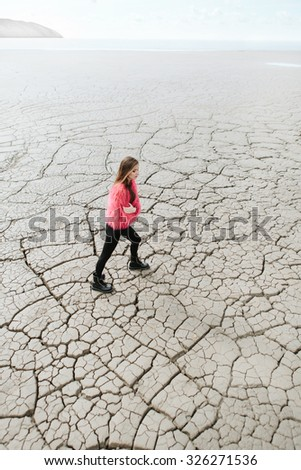 Young female model walking on dry land. Outdoors lifestyle portrait