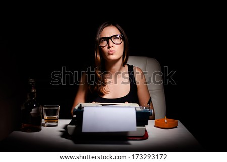 Young female novelist writing a book using typewriter - stock photo