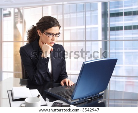 Young female office worker sits in front of her computer screen. Daylight, indoor, office. Dark cloth.