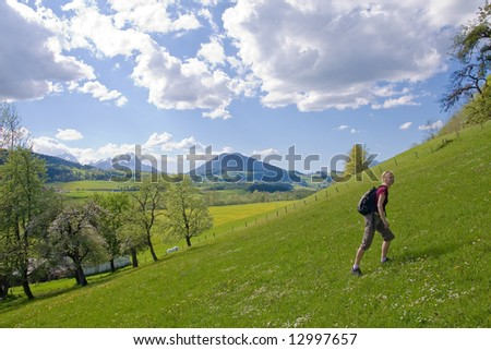young female on a meadow in the mountainous landscape