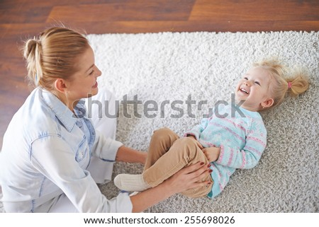 Young female or babysitter playing with little girl on the floor - stock photo