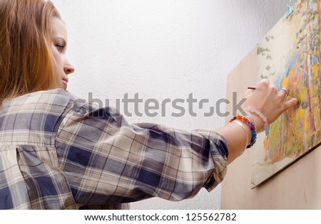 Young female painter painting landscape in her art studio. - stock photo