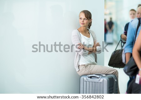 Young female passenger at the airport, about to check-in - stock photo