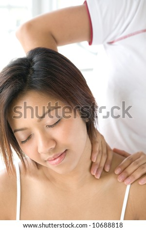 Young female patient receiving shoulder massage to ease tension from therapist - stock photo