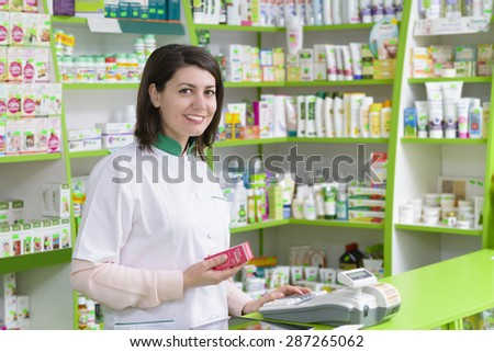 Young female pharmacist at cash register holding some medication - stock photo