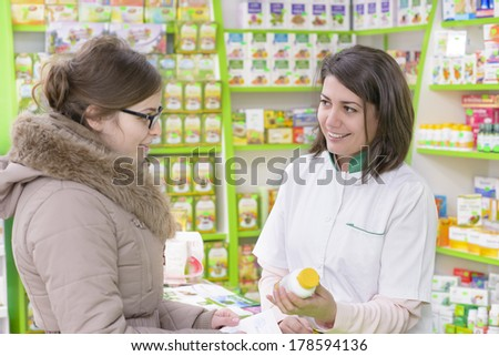 Young female pharmacist in a drugstore having conversation with a customer - stock photo
