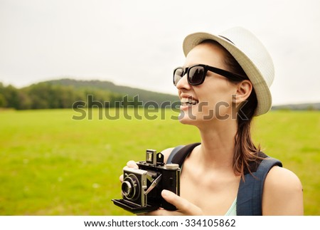 Young female photographer holding a vintage camera.