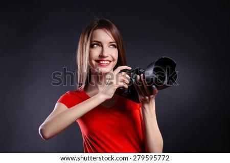 Young female photographer taking photos on black background - stock photo
