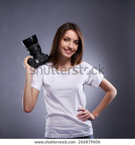 Young female photographer taking photos on grey background - stock photo