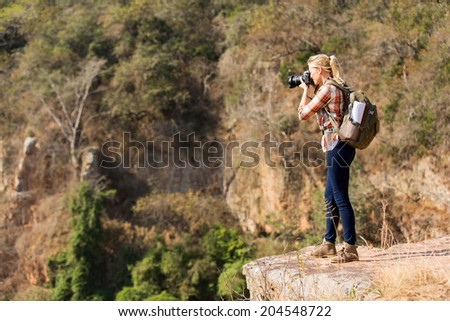 young female photographer taking photos on top of the mountain - stock photo