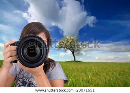 young female photographer with digital photo camera shotting landscape scene
