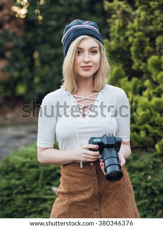 Young female photography student outdoors with digital camera and zoom lens - stock photo