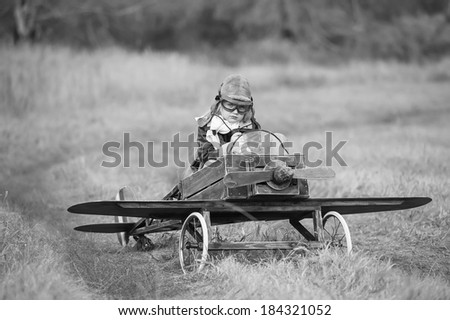 Young female pilot in a homemade plane in a field on a sunny autumn day - stock photo