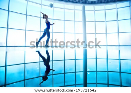 Young female playing with ball in gym on background of window - stock photo