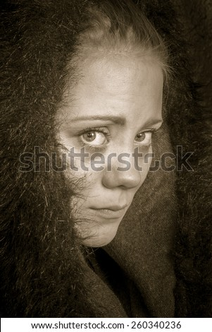 young female poor beggar in semi profile looking into the camera - stock photo
