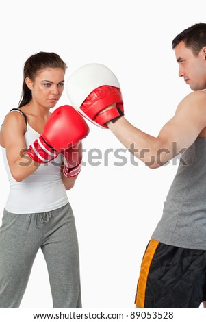 Young female practicing boxing against a white background - stock photo
