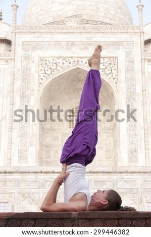Young female practising yoga asana Sarvangasana at Taj Mahal, India - stock photo