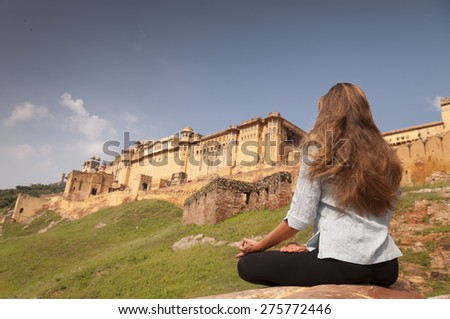 Young female practising yoga meditation at Amber fort, Jaipur, India - stock photo