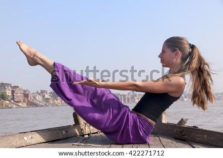 Young female practising yoga pose Navasana on the boat over Ganga river, India - stock photo