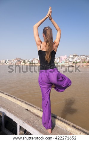 Young female practising yoga tree pose Vrksasana  on the boat over Ganga river, India