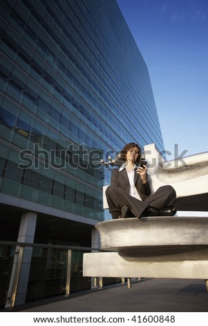 Young female professional texting short message on mobile phone during break - stock photo