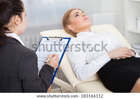 Young Female Psychiatrist Holding Clipboard Examining Businesswoman - stock photo