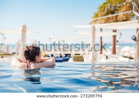 Young Female Relaxing In The Swimming Pool - stock photo