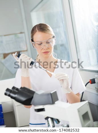 Young female researcher filling liquid into test tube in medical laboratory