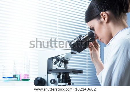 Young female researcher using microscope in the chemistry lab with laboratory glassware on background. - stock photo