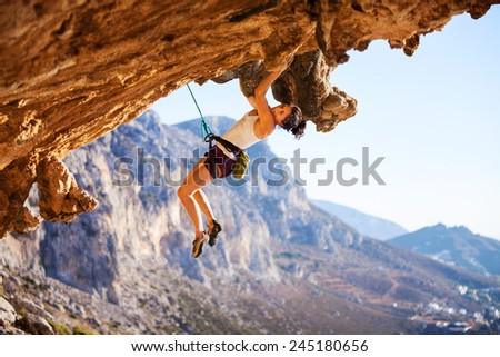 Young female rock climber on a cliff  - stock photo