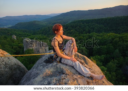 Young female rock climber sitting secured with rope on big rock at mountain peak with bare foot relaxing after climbing. Warm sunny summer evening in the mountains. Climbing equipment. - stock photo