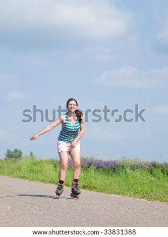 young female rollerskating on asphal road against nature