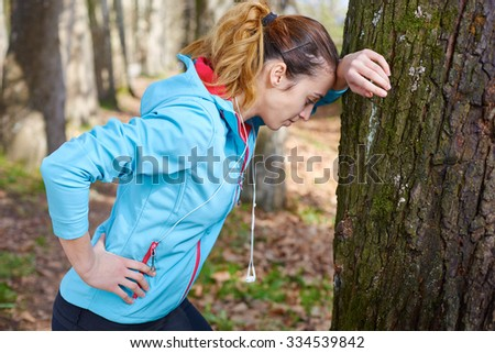 Young female runner is having break and listening to music during the run - stock photo