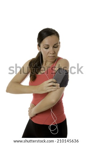 young female runner ready to run with earphones on and playing music from the mobile phone in a bangle isolated on a white background - stock photo