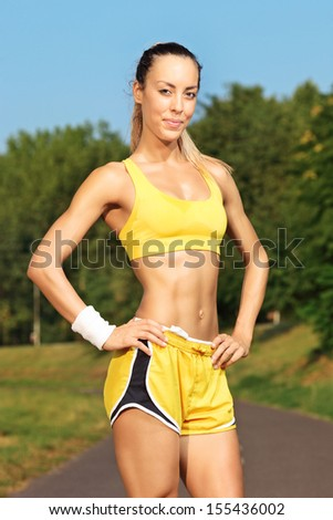 Young female runner standing on a running track and looking at camera - stock photo