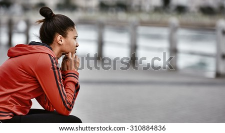 Young female runner stopping and taking a second to reflect on her active life style and how close she feels she is coming to her goals - stock photo
