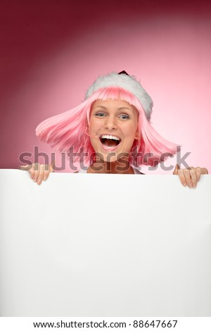 Young female santa in flaunting pink wig holding a christmas clear white card over red background - stock photo
