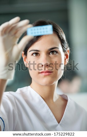 Young female scientist analyzing microscope slide in laboratory - stock photo