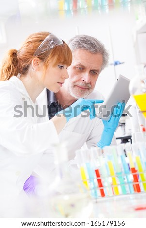 Young female scientist and her senior male supervisor checking experiment protocol at tablet laptop computer in life science research laboratory (biochemistry, genetics, forensics, microbiology..) - stock photo