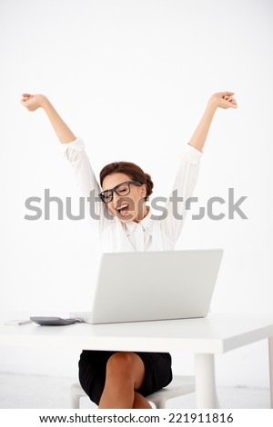 Young female secretary or accountant sitting at her desk in front of her laptop with raised arms as a gesture of happiness for the successful accomplishment of a task