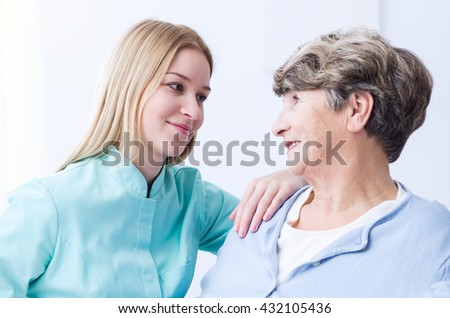 Young female senior care assistant is looking at elderly woman