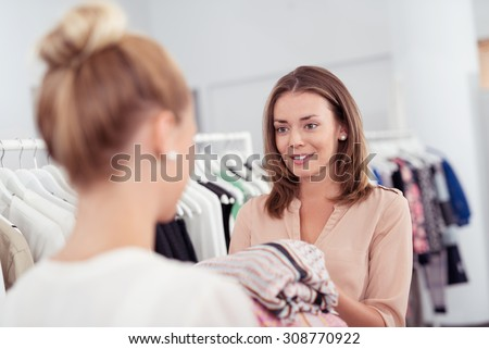 Young Female Shopper Talking to a Sales Lady While Holding Clothes Inside a Clothing Store. - stock photo