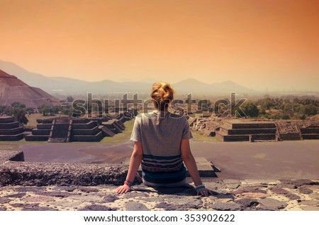 Young female sitting on top of pyramid and overlooking Teotihuacan ruins at the sunset - stock photo